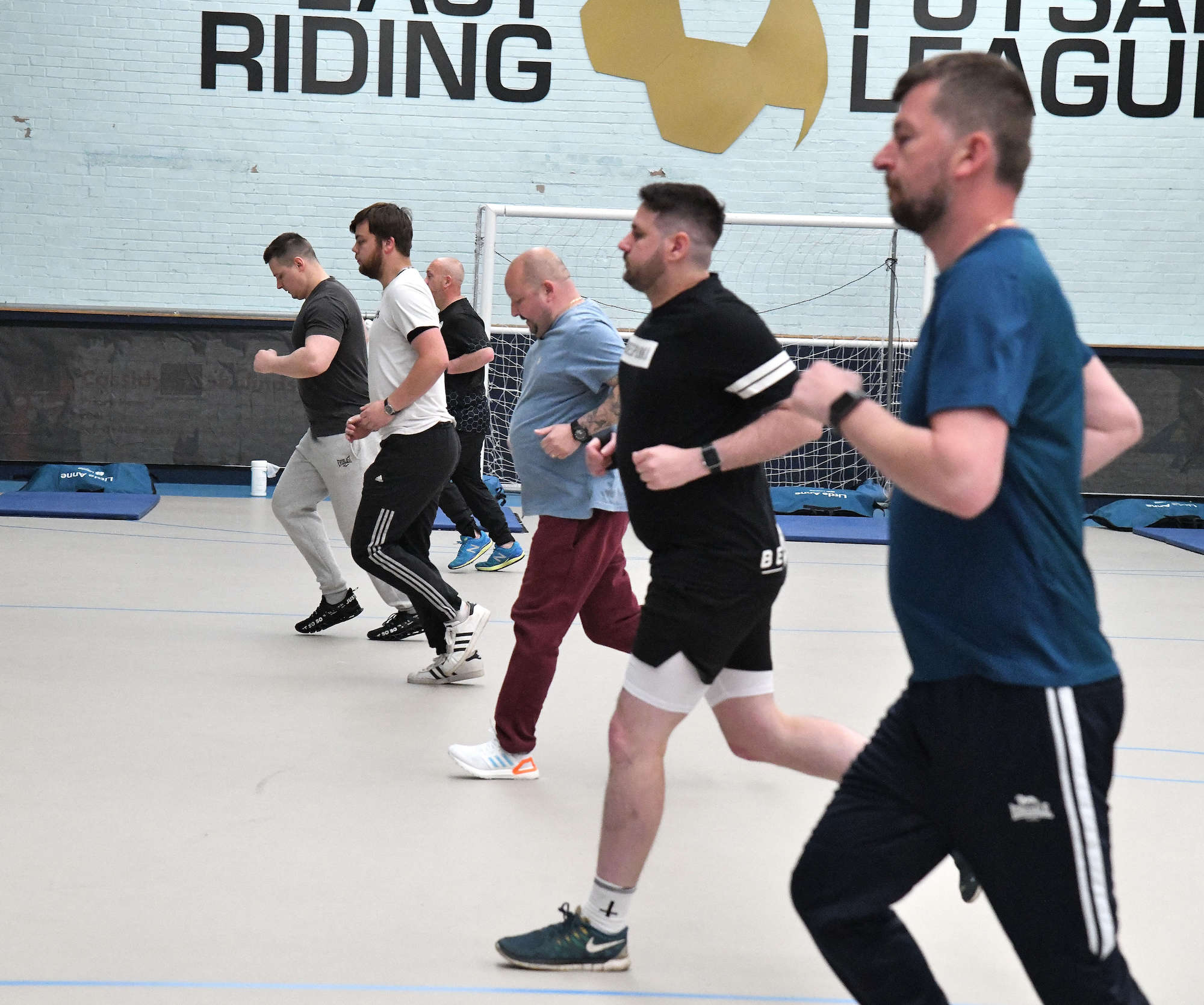 A line of men running in a sports hall